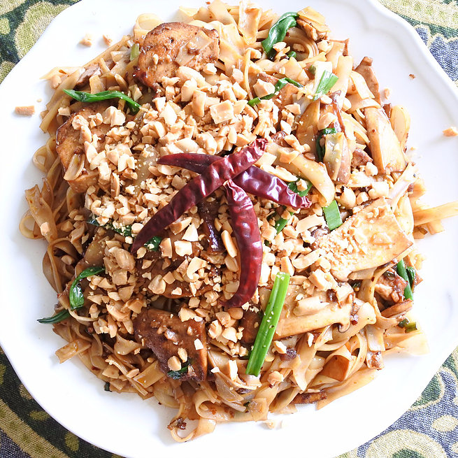 Chili and Soy rice noddles topped with dried red chiles and chopped peanuts