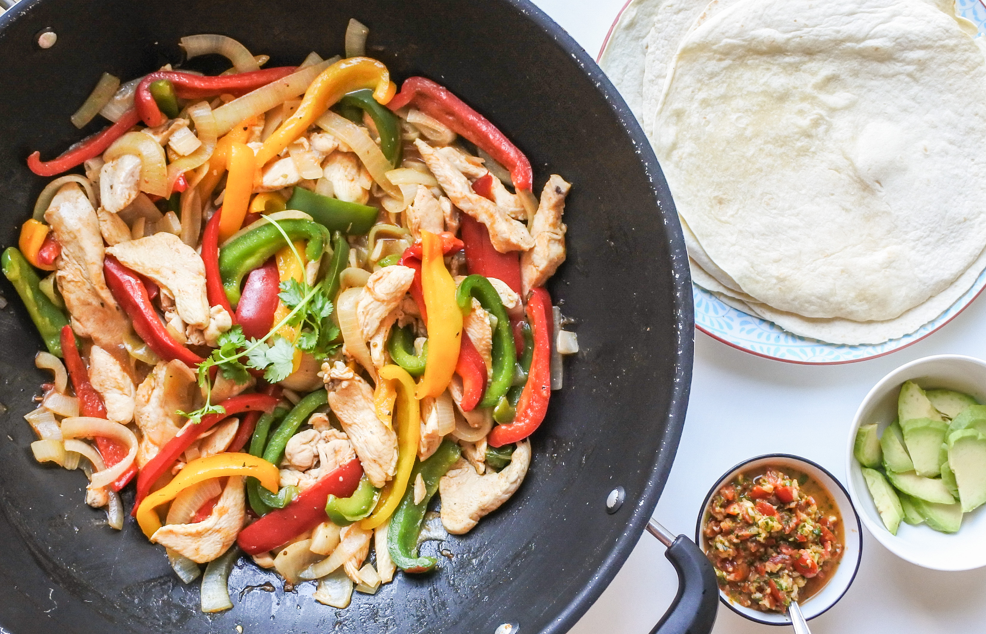 A skillet of chicken fajitas served alongside flour tortillas, salsa and avocado